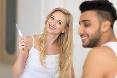 Junge Paare, die im Bett, glückliche Lächeln-Frauen-Show aufgeregter überraschter Mann-Positiv-Schwangerschaftstest sitzen stockfotos