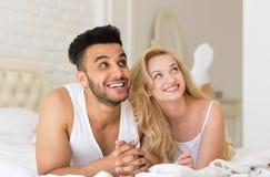 Junge Paare, die im Bett, im glückliches Lächeln-hispanischen Mann und in den Frauen-Liebhabern im Schlafzimmer liegen Lizenzfreies Stockbild