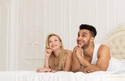 Junge Paare, die im Bett, im glückliches Lächeln-hispanischen Mann und in den Frauen-Liebhabern im Schlafzimmer liegen Stockfoto