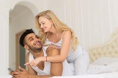 Junge Paare, die im Bett, im glückliches Lächeln-hispanischen Mann und in der Frau verwendet Zell-Smart-Telefon liegen Stockfoto