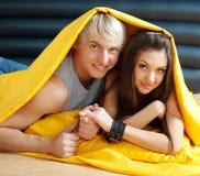 Junge Paare, die im Bett küssen Stockbild