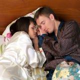 Junge Paare, die im Bett schlafen Stockbilder