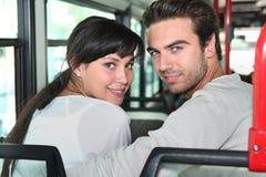Junge Paare, die im Bus sitzen Lizenzfreie Stockfotos
