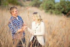 Junge Paare, die im hohen Gras spielen Lizenzfreies Stockbild