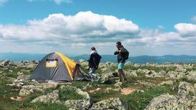 Junge Paare, die im Lager in der Natur an einem sonnigen Sommertag stillstehen Zelt auf einer grünen Wiese in den Bergen Touriste stock footage