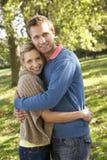 Junge Paare, die im Park aufwerfen Lizenzfreie Stockbilder