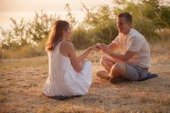Junge Paare, die im Park sitzen stockbilder