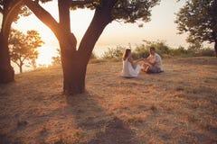 Junge Paare, die im Park sitzen lizenzfreie stockfotografie