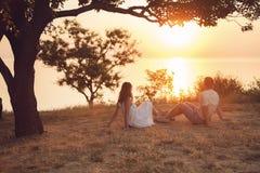 Junge Paare, die im Park sitzen lizenzfreies stockfoto