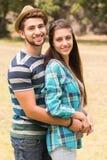Junge Paare, die im Park umarmen Stockbild