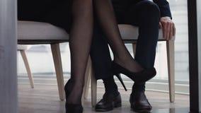 Junge Paare, die im Restaurant mit den Beinen unter der Tabelle flirten stock video footage