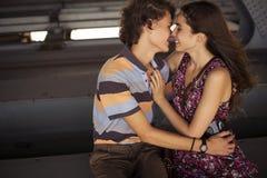 Junge Paare, die im Sommertageslicht auf einem Brücke construc küssen Stockfotografie