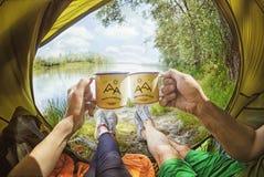 Junge Paare, die im Zelt und im trinkenden Tee beim Schauen auf dem Desna-Fluss sitzen Lizenzfreies Stockbild