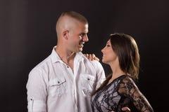 Junge Paare, die 20 Jahre alte aufwerfende schwarze Hintergrund umarmen Lizenzfreie Stockfotos