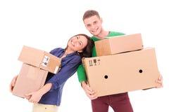 Junge Paare, die Kästen halten Bewegen auf eine neue Wohnung oder ein Haus Lizenzfreie Stockfotografie