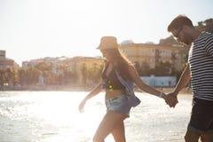 Junge Paare, die am Küstenhändchenhalten gehen stockfotografie