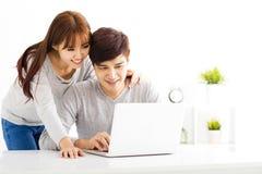 junge Paare, die Laptop im Wohnzimmer betrachten Stockbild