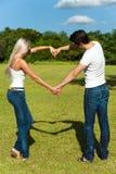 Junge Paare, die Liebeszeichen mit den Armen machen. Stockbild