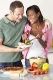 Junge Paare, die Mahlzeit in der Küche essen Stockbilder