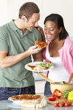 Junge Paare, die Mahlzeit in der Küche essen Lizenzfreie Stockfotos