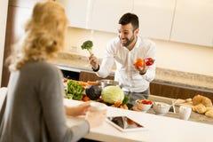 Junge Paare, die Mahlzeit in der Küche vorbereiten Lizenzfreies Stockbild