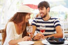 Junge Paare, die Mahlzeit Restaurant im im Freien genießen Lizenzfreie Stockfotografie