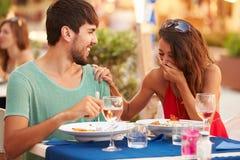 Junge Paare, die Mahlzeit Restaurant im im Freien genießen Stockfoto