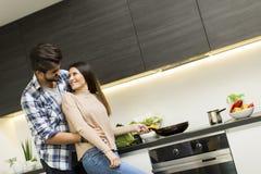 Junge Paare, die Mahlzeit vorbereiten Stockbilder