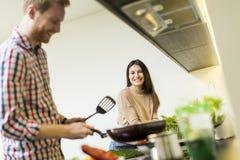 Junge Paare, die Mahlzeit vorbereiten Stockbild