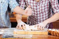 Junge Paare, die Mehl addieren und Teig auf der Küche kneten Lizenzfreie Stockfotografie