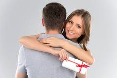 Junge Paare, die mit dem eingewickelten Presentholding vorhanden mit Band umarmen Lizenzfreie Stockfotos