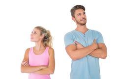 Junge Paare, die mit den Armen gekreuzt aufwerfen Lizenzfreie Stockbilder