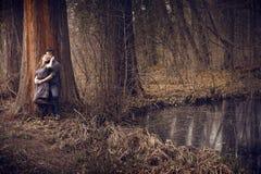 Junge Paare, die mit der Neigung im Freien umarmen Lizenzfreie Stockfotografie