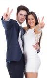 Junge Paare, die mit Sieggeste lächeln Stockfotografie