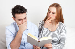 Junge Paare, die mit einem Buch lernen Lizenzfreie Stockfotos
