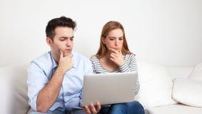 Junge Paare, die mit einem Notizbuch lernen Stockbild