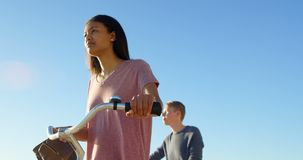 Junge Paare, die mit Fahrrad auf dem Strand 4k gehen stock video