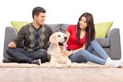 Junge Paare, die mit ihrem Hund sitzen Lizenzfreie Stockfotos