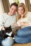 Junge Paare, die mit Katze auf Sofa sitzen Stockfotos