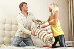 Junge Paare, die mit Kissen kämpfen lizenzfreies stockfoto