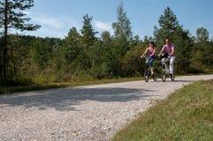 Junge Paare, die mit modernen kleinen Efahrrädern radfahren stockfotos
