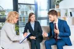 junge Paare, die mit Psychologen während der Therapie sprechen Lizenzfreies Stockbild