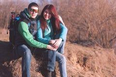 Junge Paare, die mit Rucksäcken wandern Lizenzfreie Stockfotos