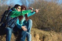 Junge Paare, die mit Rucksäcken wandern Stockfotos