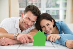 Junge Paare, die Modell des grünen Hauses halten Lizenzfreies Stockbild