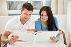 Junge Paare, die Modell des grünen Hauses halten Stockbild