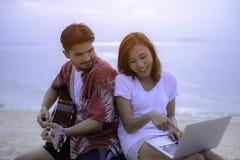 Junge Paare, die Musik spielen und zusammen singen stockbild