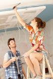 Junge Paare, die nach Hause erneuern stockbilder