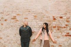 Junge Paare, die nahe der Backsteinmauer in der Stadt aufwerfen Stockbilder