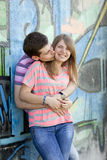 Junge Paare, die nahe Graffitihintergrund küssen. Stockfotografie